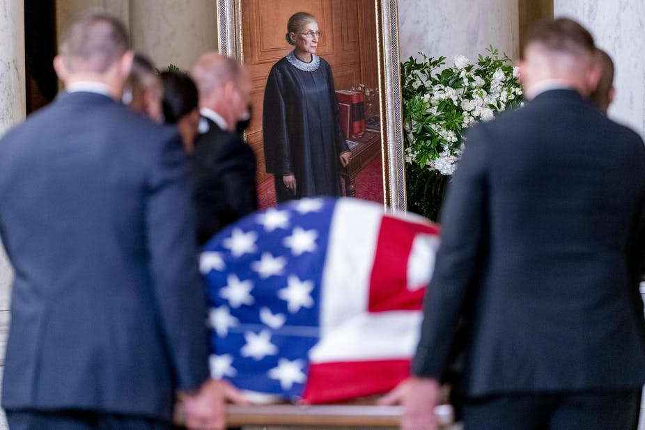 The flag-draped casket of Associate Justice Ruth Bader Ginsburg, carried by Supreme Court police officers, arrives in the Great Hall at the US Supreme Court