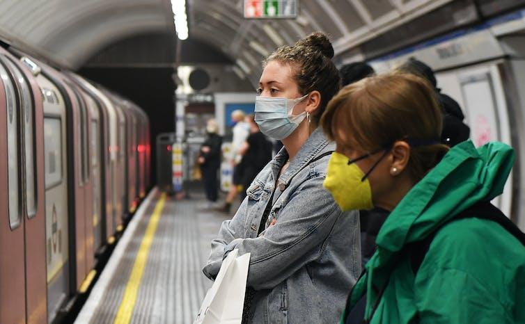 Commuters wearing face masks on a London Underground station platform.