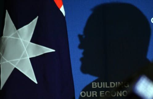 A silhouette of Scott Morrison, cast against an Australia flag