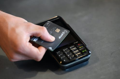 A credit card being tapped against an EFTPOS machine