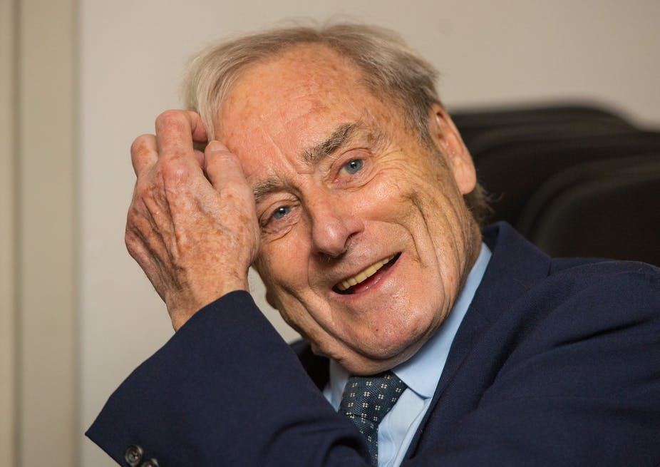 Elderly man smiling and combing his hair with his hand.