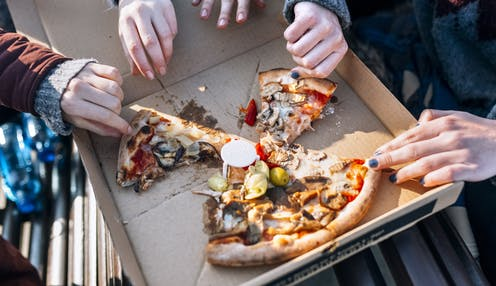 Overhead shot of five hands reaching for four slices of pizza.