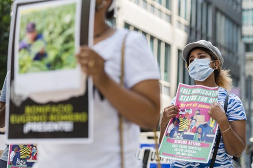 A woman wearing a mask carries a sign calling for full immigration status for seasonal workers.