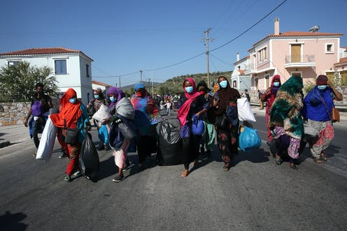 Women wearing headscarves and masks carry their belongings down a sunny street.