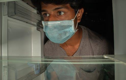 A man wearing a mask opens an empty fridge.