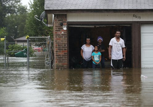 A family waits in their garage to be rescued during Hurricane Harvey.