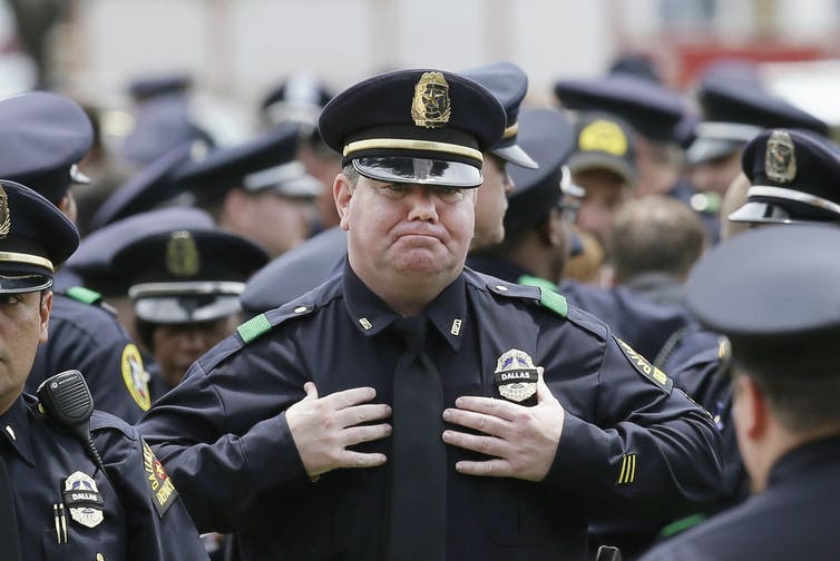 A police officer fights back tears at a memorial service.