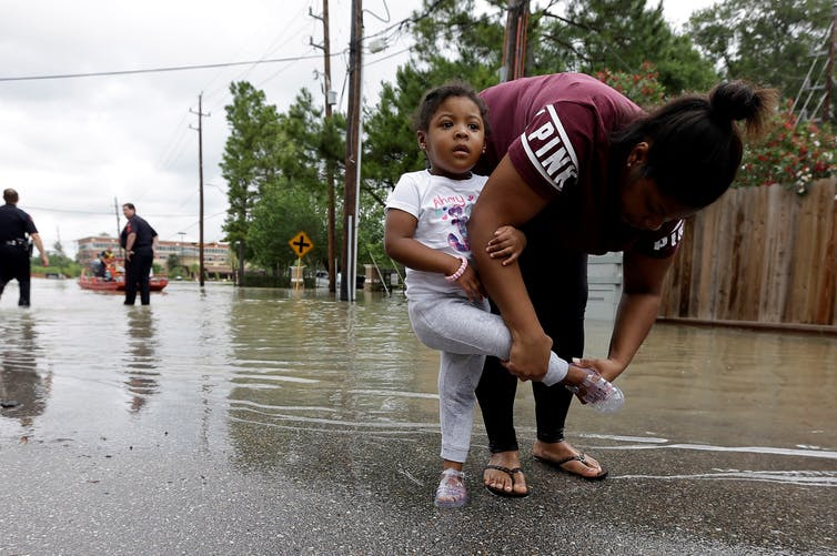 A woman puts her daughter's shoe on after they were rescued from a flooded apartment complex.
