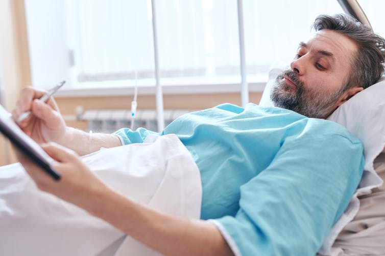 Man lying down in hospital bed signing papers