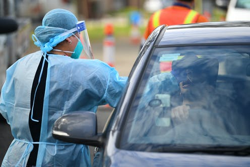 A woman in PPE performs a COVID test on a person in their car.