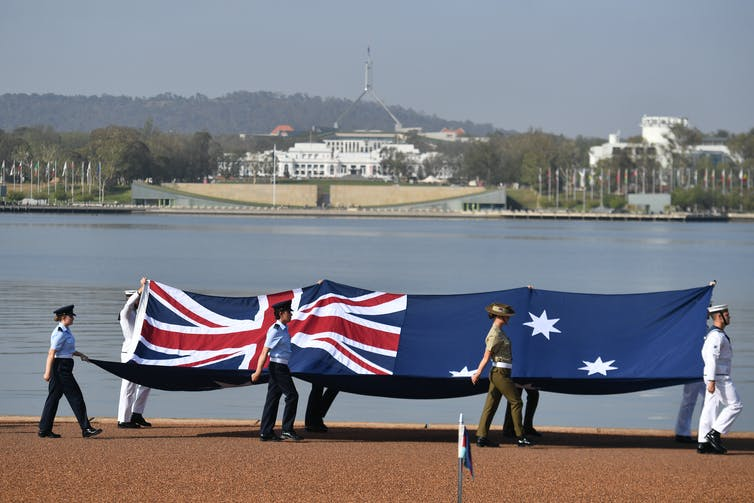 Armed forces members carry a large Australian flag with Parliament House in the background