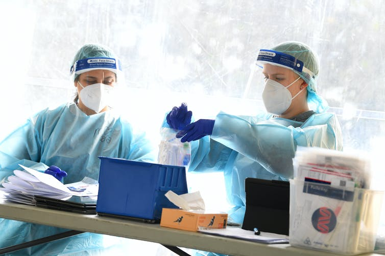 Two health-care workers wearing PPE are processing test samples.