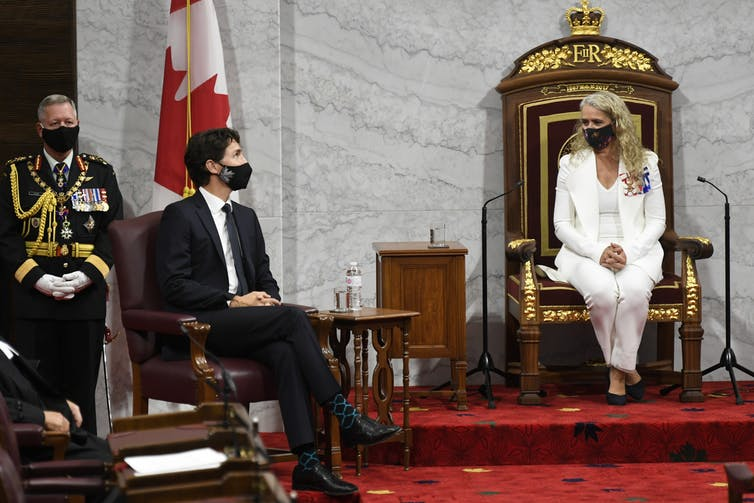 Gov. Gen. Julie Payette, wearing a white suit, sits in the ornate chair reserved for the governor general, on a raised platform. The prime minister sits in front of her on the left, with a man wearing a uniform behind him. They all wear black face masks.
