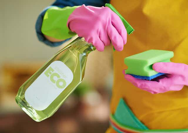 Someone wearing rubber gloves and spraying liquid from a spray bottle marked eco.