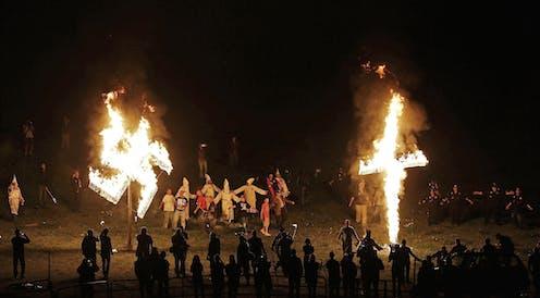 A burning swastika and cross at a Ku Klux Klan rally.
