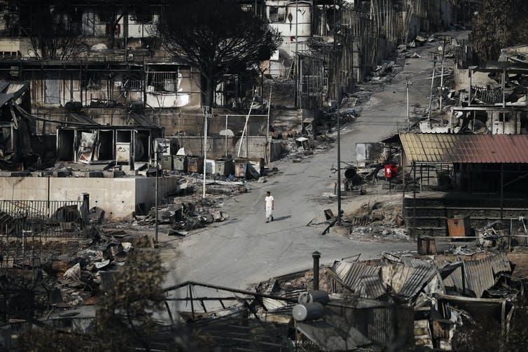 A man walks down a road surrounded by blackened out tents and shacks.