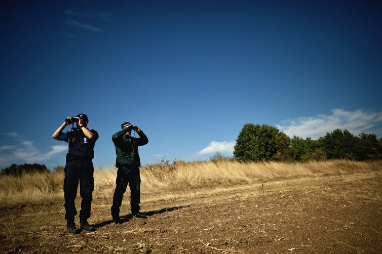Two men in dark uniform look through binoculars.