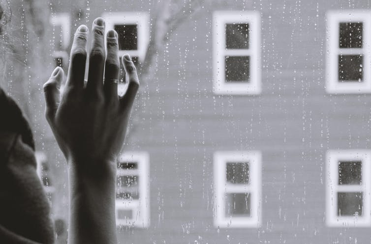 A woman's hand rests against a rain-spattered window pane.