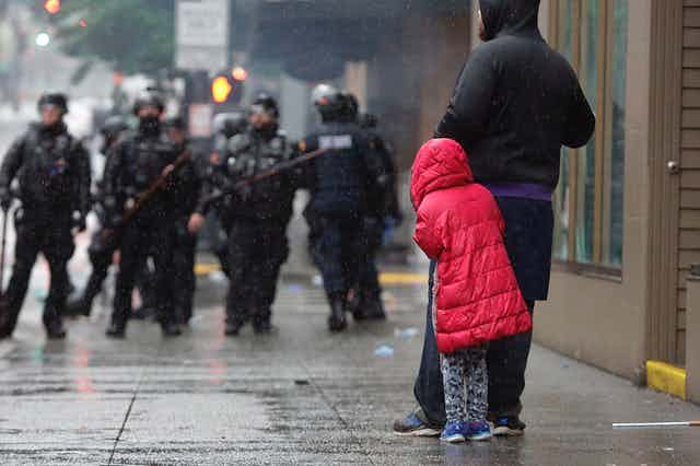 A girl cowers behind an adult in front of police in riot gear at a protest over the death of George Floyd.