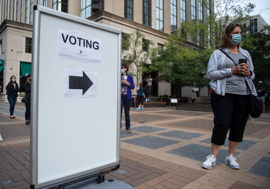 A woman with a mask stands next to a sign pointing to a voting station.