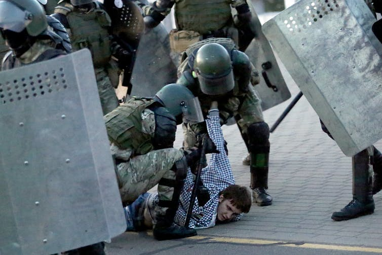 Law enforcement officers detain a man during an opposition rally to protest against the presidential inauguration in Minsk on Sept. 23.