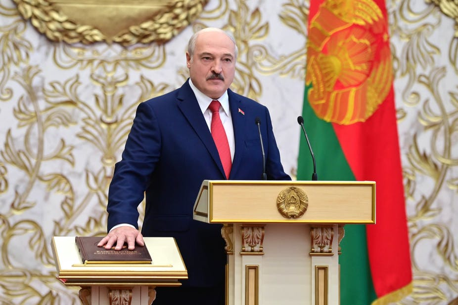 Lukashenko stands behind a lectern with his hand on a brown leather-bound book