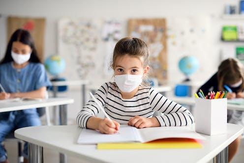 Schoolchildren wearing face masks sit at their socially-distanced desks.