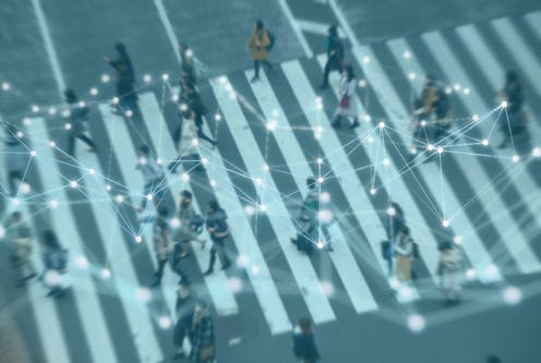 A network appears over a blurred birds-eye photograph of people on a crosswalk