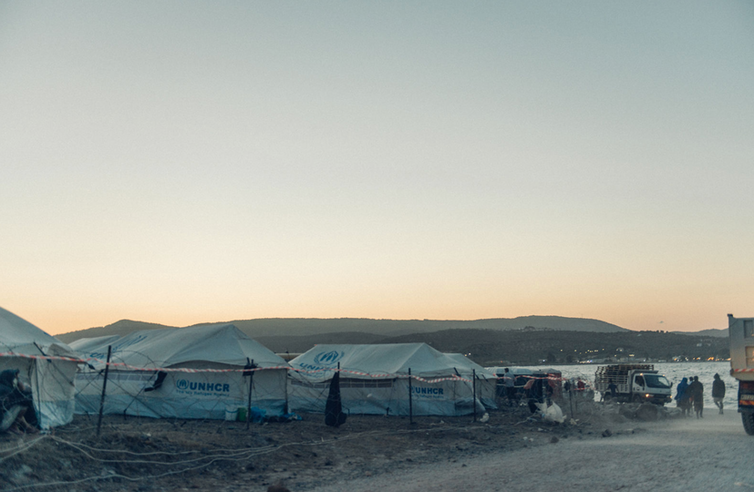 Tents are seen at dawn behind a fence.