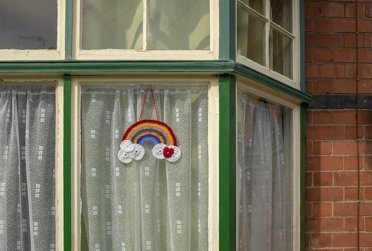 A crocheted rainbow hangs in a window.