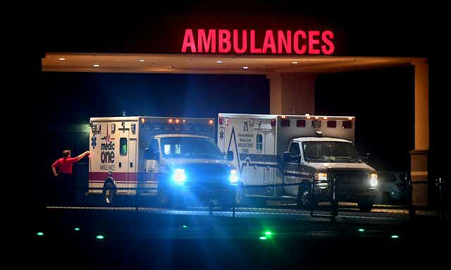 Two ambulances with lights on at nighttime.