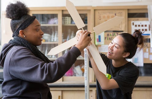 Two students handle a hand-made wind turbine.