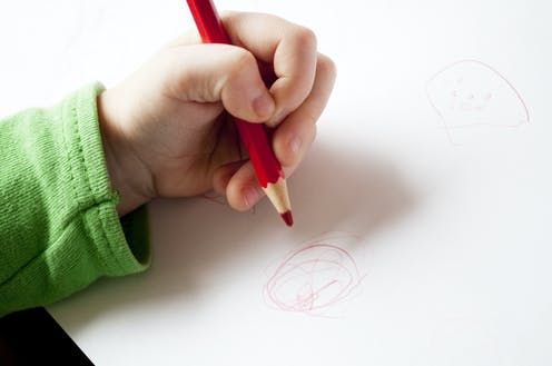 A child's left hand holding a pencila and drawing on a piece of paper.