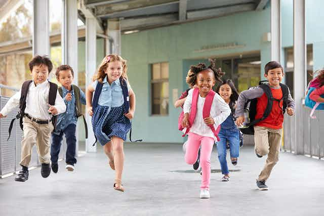 Primary school kids running in school.