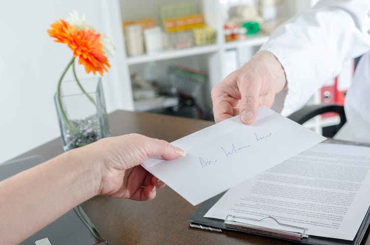 A doctor handing a patient a referral letter