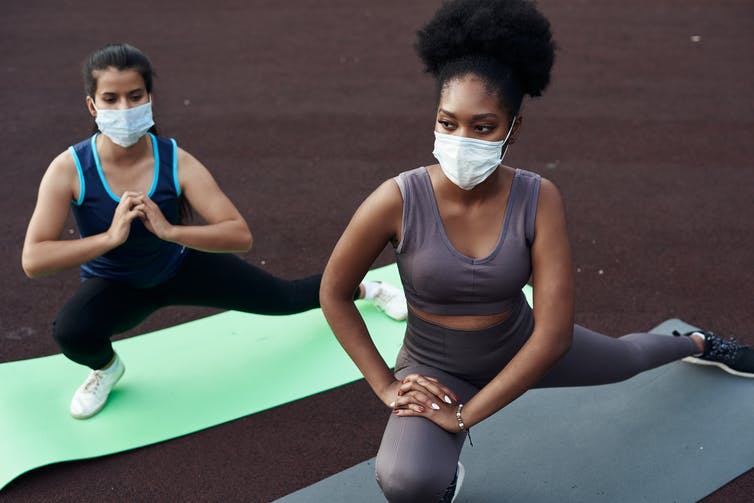 Women doing yoga wearing masks