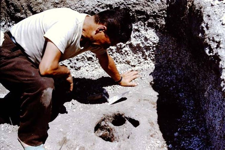 An old photograph, a man leans over a hole in the dirt.