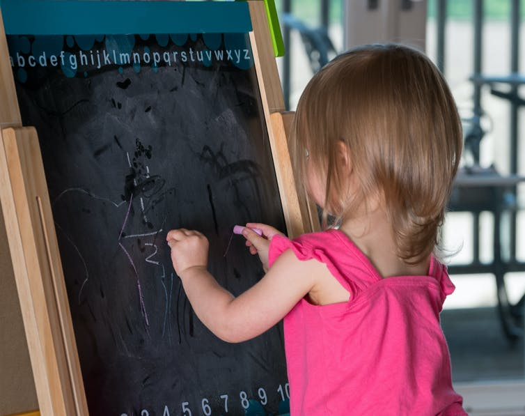 A young girl writing on a blackboard with both hands at the same time.