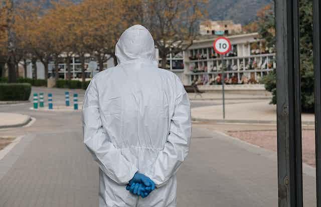 Persona de espaldas con traje de protección y guantes en un cementerio.