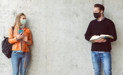 Male and female students wearing masks standing a distance from eachother.