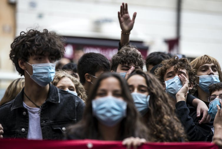 Students wearing facemasks attend a protest.