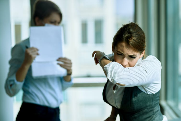 Young women coughs into her arm while colleague puts papers in front of her face.