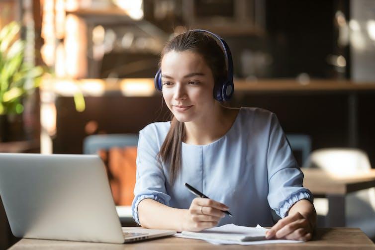 امرأة ترتدي سماعات رأس ممسكة بقلم تنظر إلى شاشة الكمبيوتر المحمول
