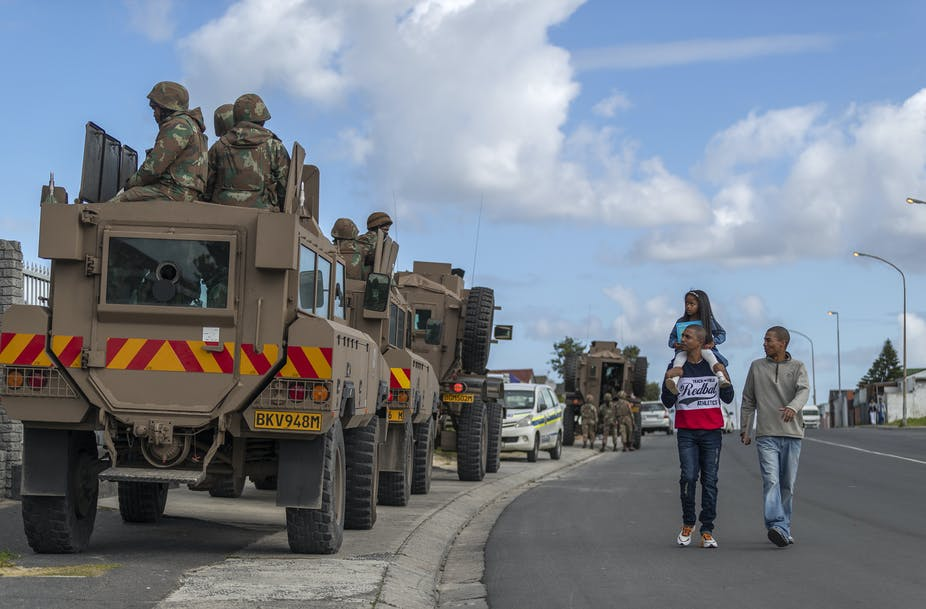 Two young man, one carrying a child on his shoulders, walk past a South African military convoy on a street in of Cape Town.