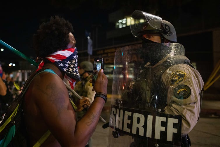 Man with American flag bandana talks to policeman with shield marked sheriff