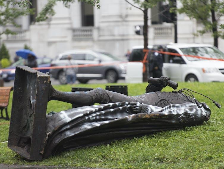 A statue of Sir John A. MacDonald lies on the ground.
