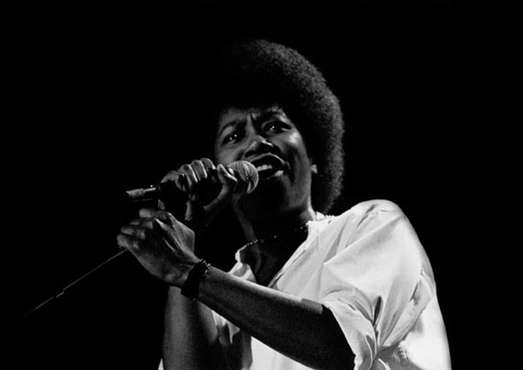 Black woman in white t-shirt singing into a microphone.