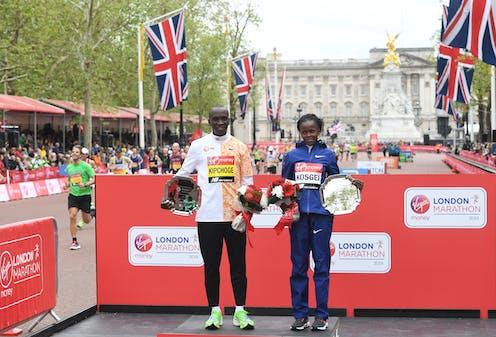 London Marathon men's race winner, Eliud Kipchoge, and women's race winner, Brigid Kosgei pose at the medal ceremony during the 2019 London Marathon.