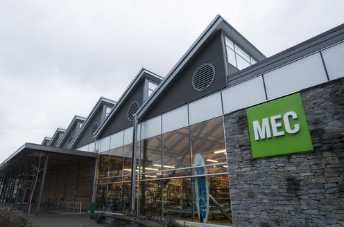 The green MEC sign is seen outside a gray stone and glass building.