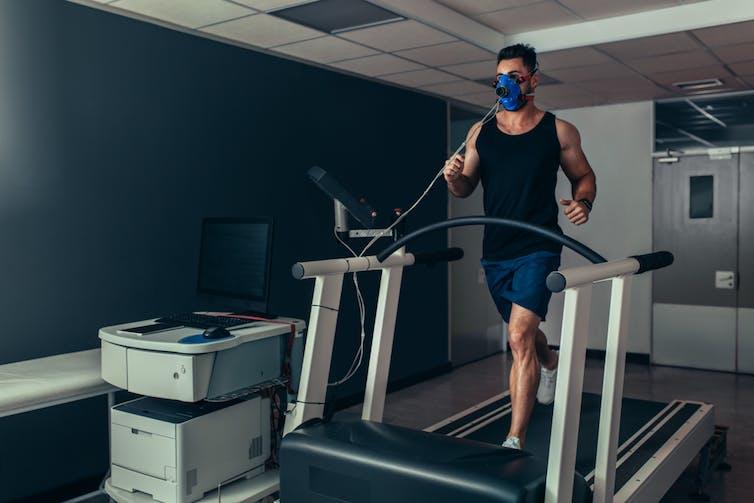Male athlete having VO2 max test on treadmill.